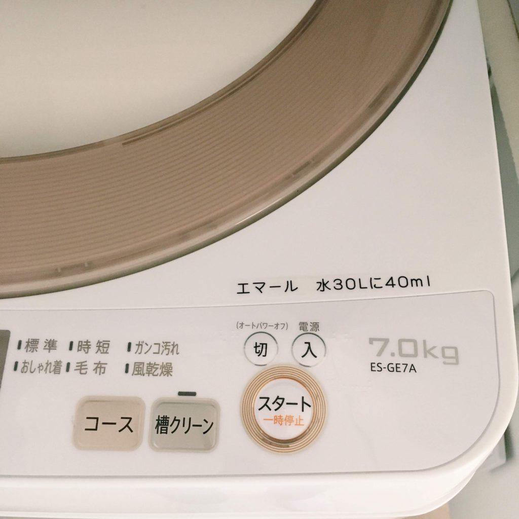 洗濯機に、「エマール 水30Lに40ml」と書かれたテープが貼られています。