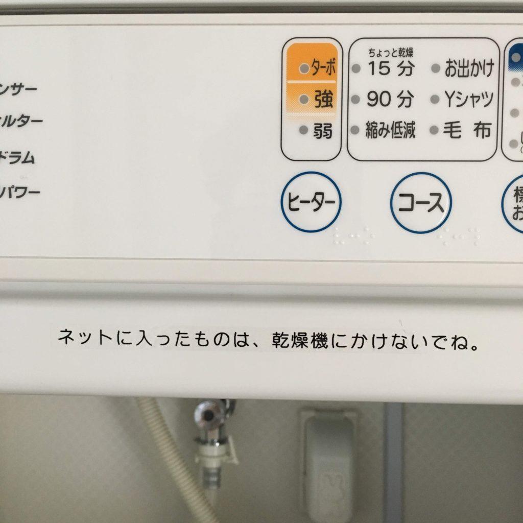 「ネットに入ったものは、乾燥機にかけないでね。」と書かれたテープが乾燥機に貼られています。