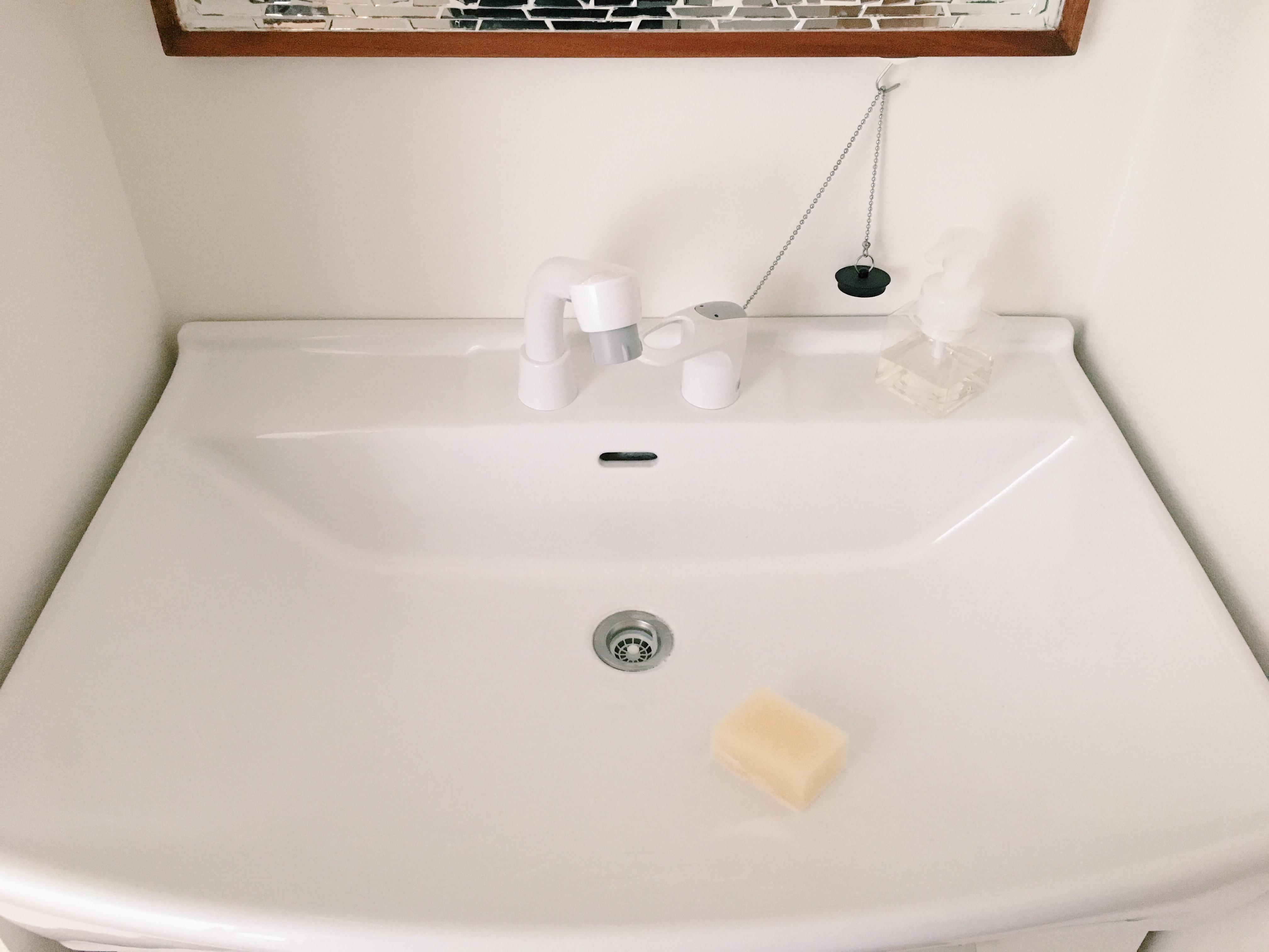 洗面台の中をスポンジで洗っています。