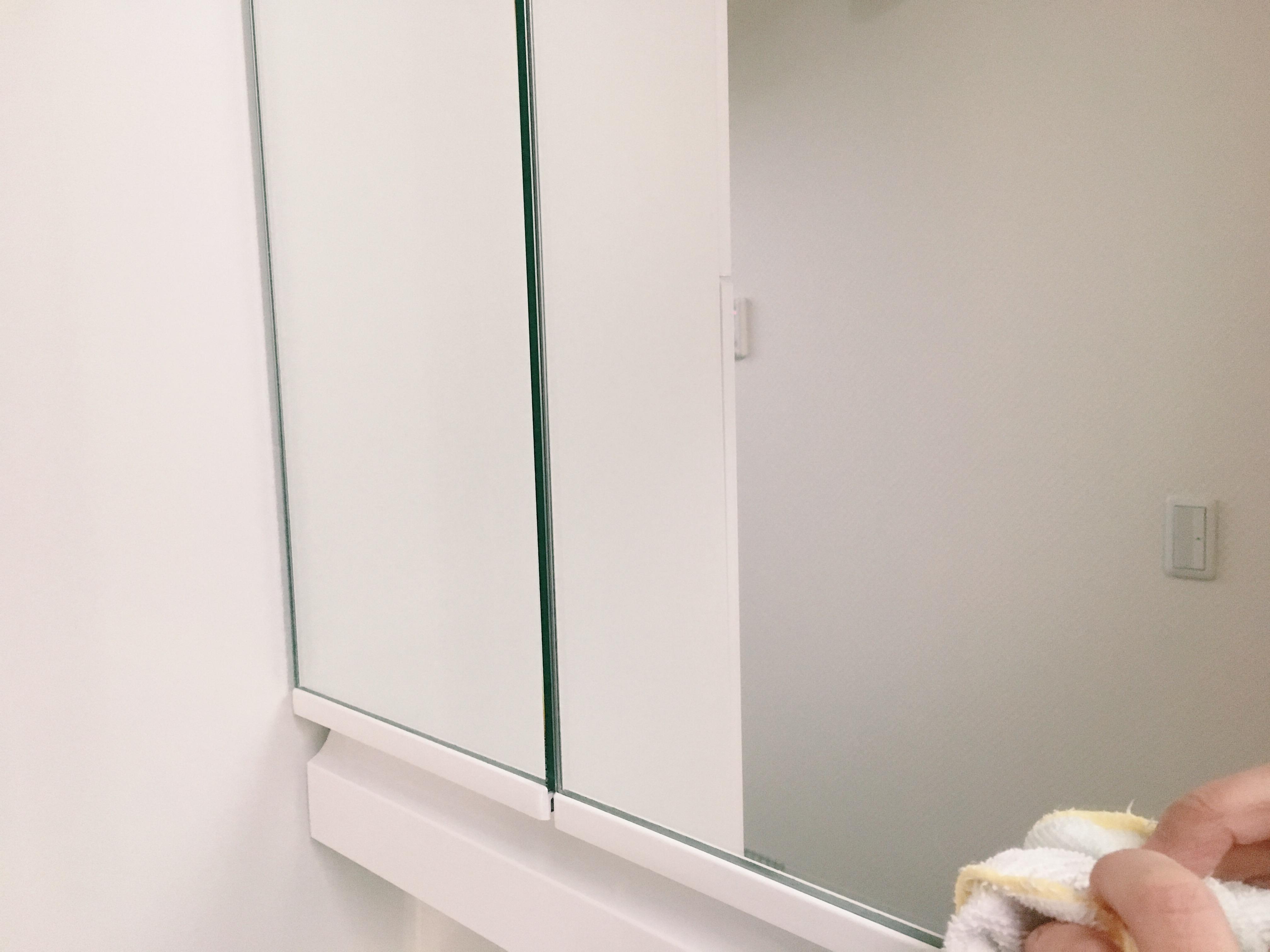 洗面台の鏡を拭いています