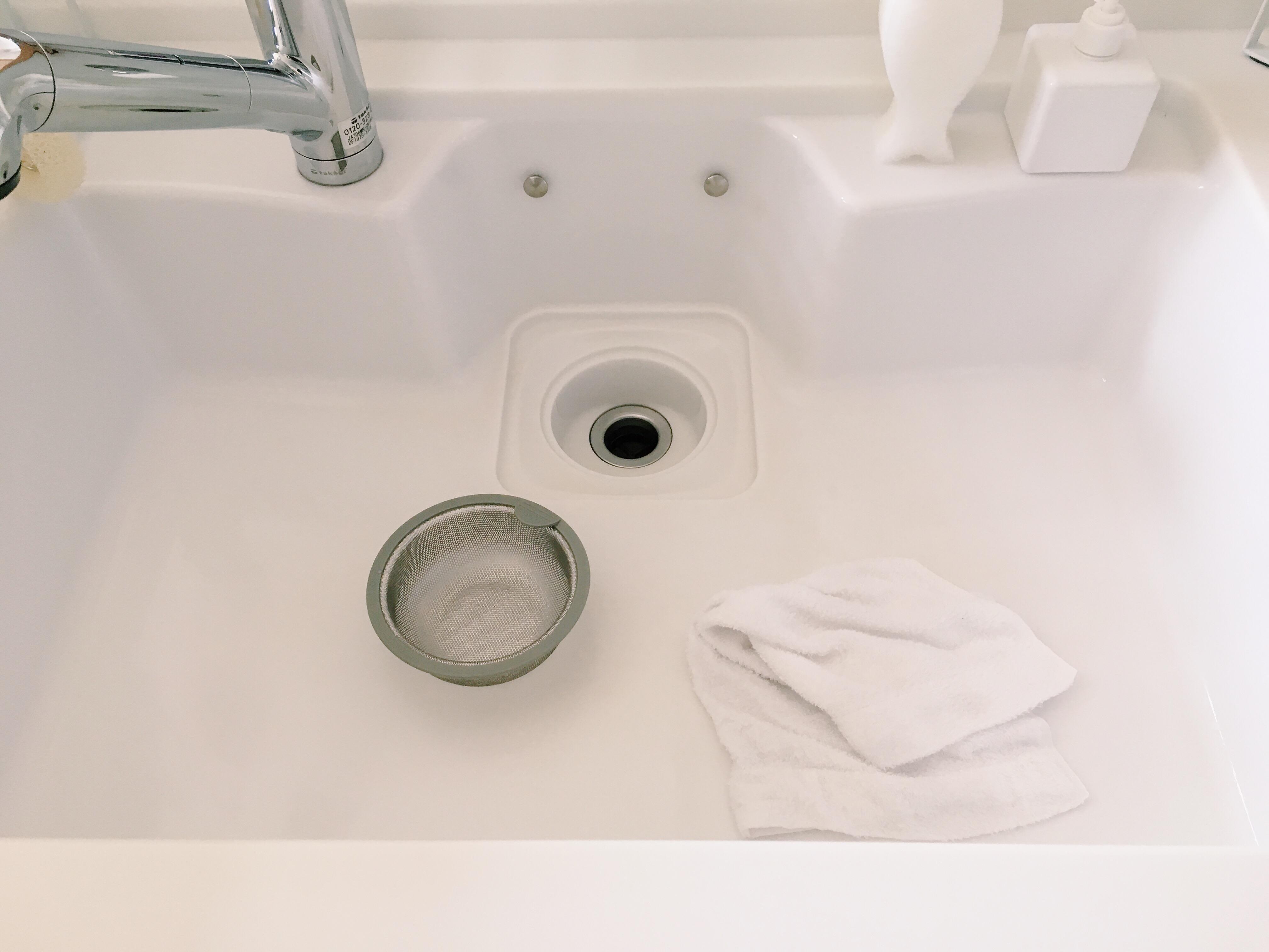 シンク内をタオルで拭き上げています。